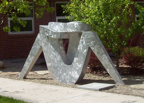 An outdoor aluminum sculpture of an abstracted embrace