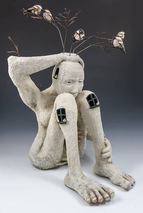 Sculpture of human figure as bird nest with branches and birds