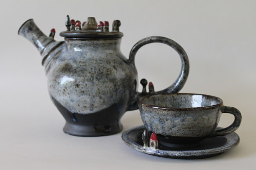 A teapot with a tiny village sculpted on top