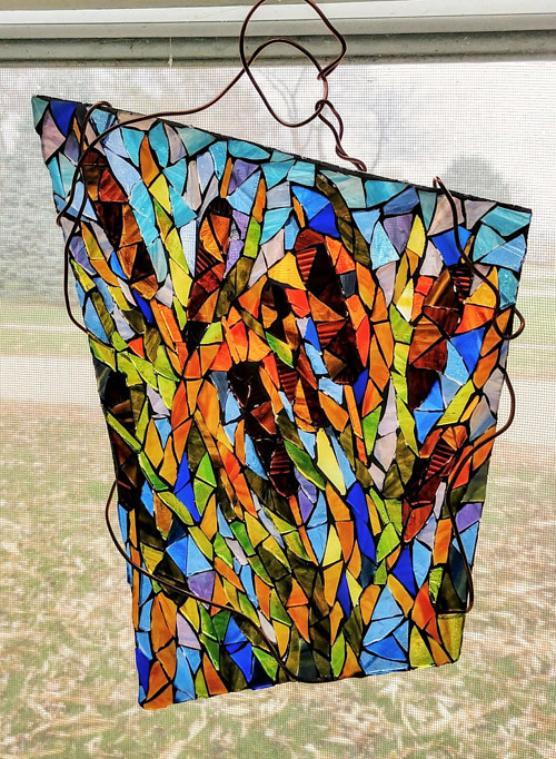 A hanging glass mosaic of autumnal cattails