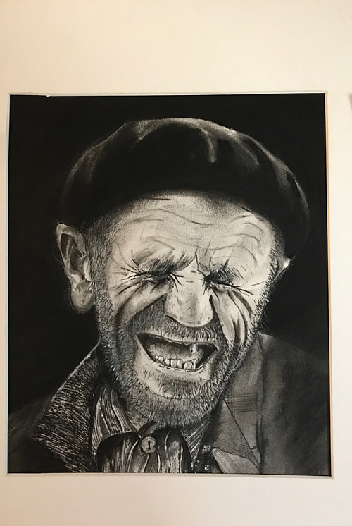 A charcoal drawing of a smiling homeless man