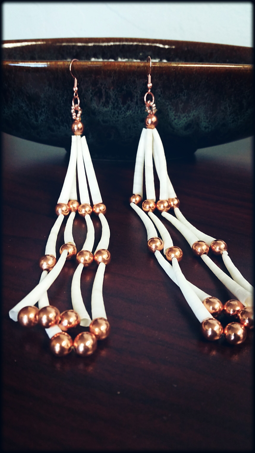 A pair of earrings made from carved dentalium