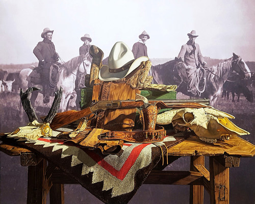 A painting of a table full of objects in front of a cowboy backdrop