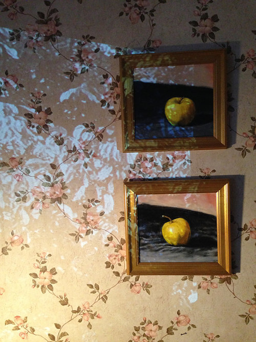A detail from an installation artwork featuring paintings of apples