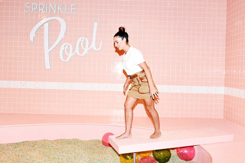 A photo of a woman at the Museum of Ice Cream sprinkle pool