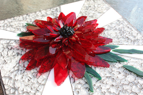 A mosaic of a red dahlia made with glass and other materials