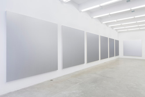 A photo of several silver gradient canvases on a gallery wall