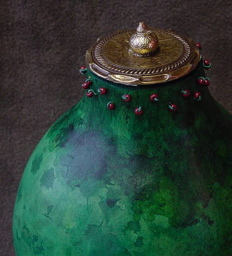 A gourd painted green with a decorative cap