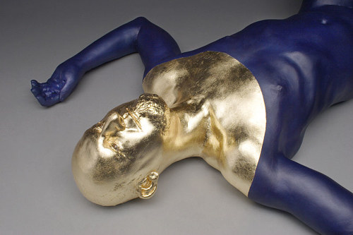 A sculpture of a man lying on the floor with a gold face