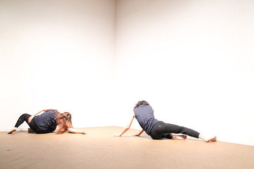 A photograph of two performers dancing in an art gallery