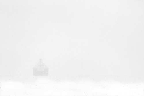 A photograph of a shed barely visible through snow