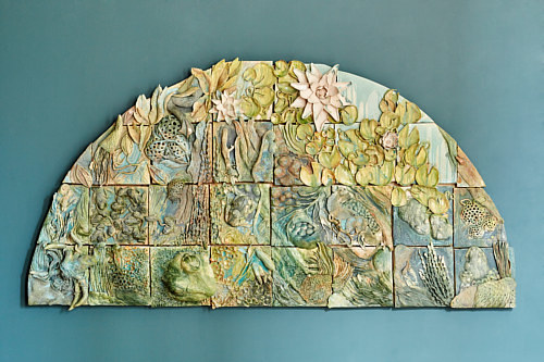 A wall-hanging artwork with the forms of plants and flowers