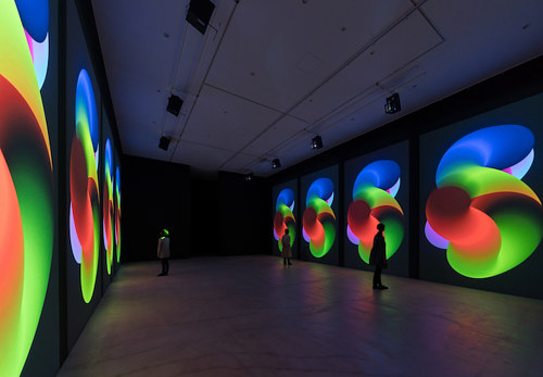 A photo of an installation with changing images projected onto walls