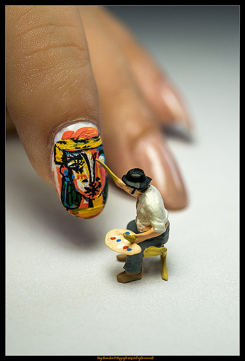Artist painting a colorful face on nail