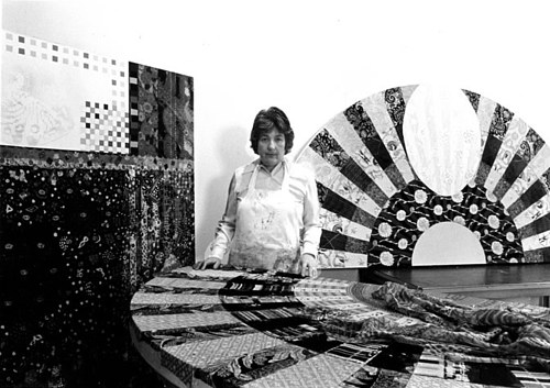 A photo of Miriam Schapiro at work in her studio