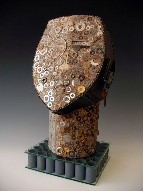 A sculpture adorned with a variety of small metallic pieces