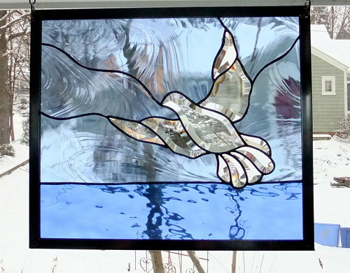 A stained glass portrait of a dove flying
