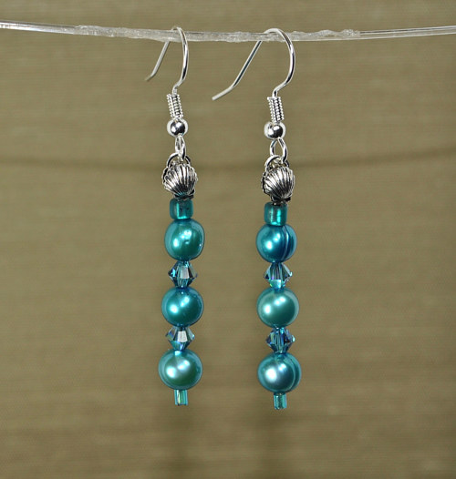 A pair of earrings made with turquoise beads