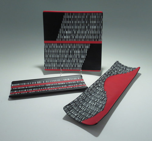 A series of glass artworks with a distinct red and black pattern