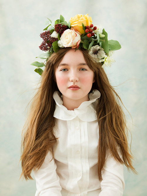 A photo of a model wearing a floral garland hat