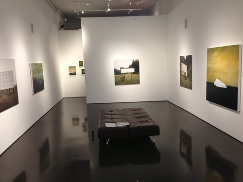 Photo of paintings hanging in gallery