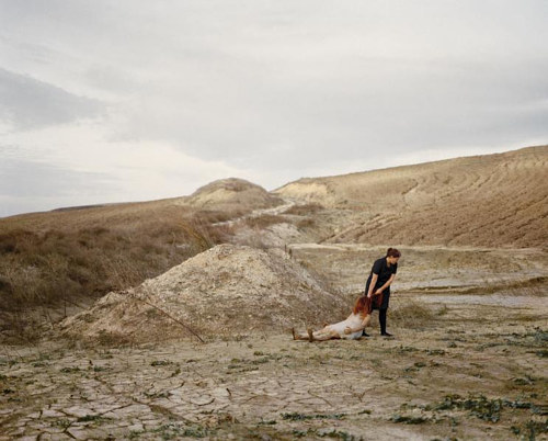 A photograph of a person dragging a figure across dry ground