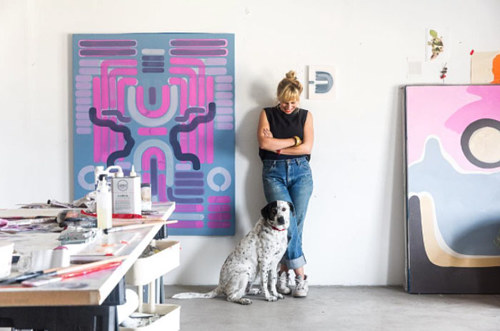 A photo of Lily Stockman and her dog in her studio