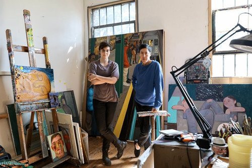 A photo of Nicole Eisenman in her studio with Grace Dunham