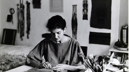 A photograph of a young Sheila Hicks in her studio