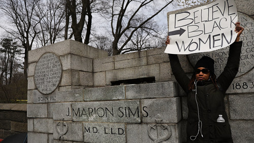 A photo of a woman holding a protest sign in front of the former location of a statue of J. Marion Sims