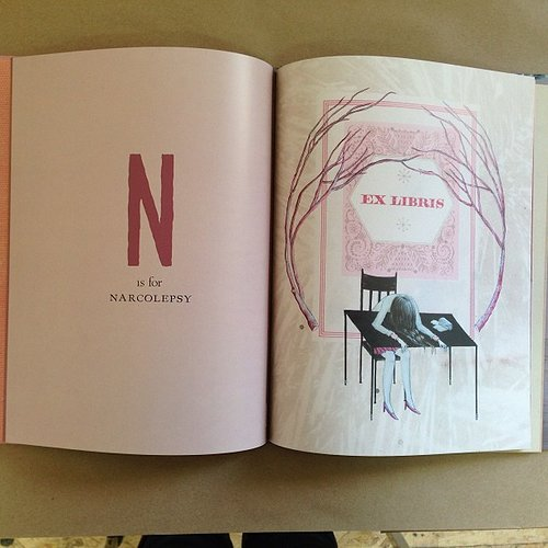 Open book with to letter N and girl on table