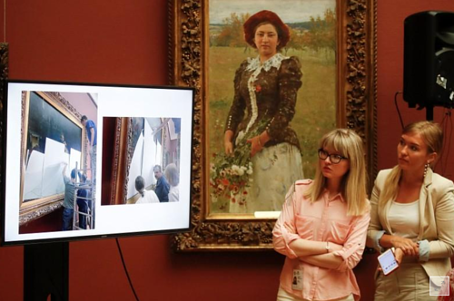 Two women view a screen at a media conference about the damaged Russian painting