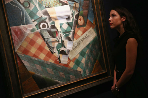 A photo of a Christie's auction house employee looking at a painting up for sale
