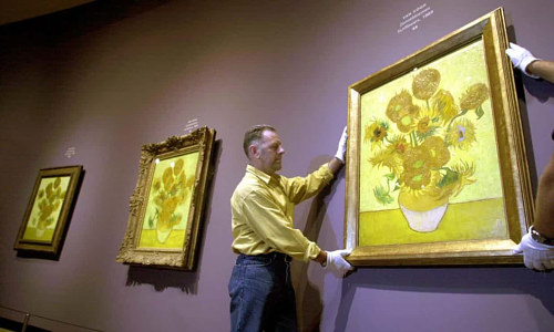 Two experts handle Van Gogh's Sunflowers at a museum in Amsterdam