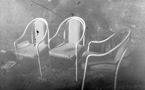A photograph of three chairs sitting outdoors