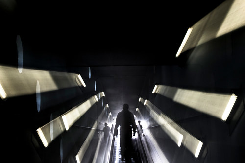 A photograph of a figure running down a dark tunnel