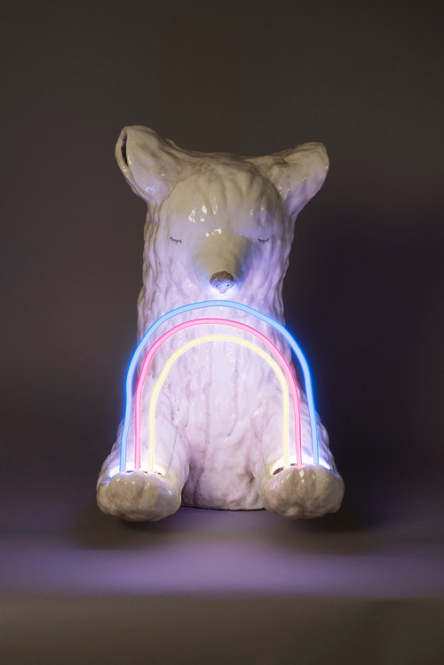 A ceramic polar bear holding a neon light rainbow