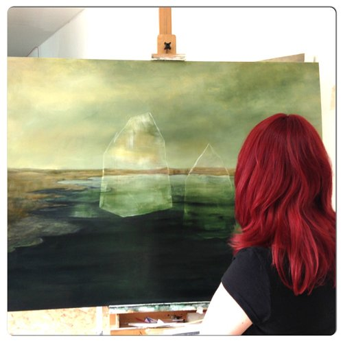 Red haired woman visiting an artist's studio and looking at a painting