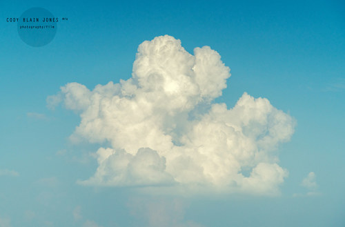 A photograph of a white fluffy cloud