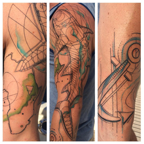 An upper-arm tattoo of a shark and other wireframe shapes
