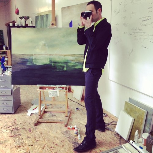 man taking a photograph in front of a painting
