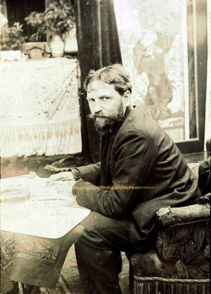 Alphonse Mucha seating in his art studio