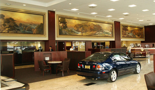 A series of framed landscape paintings inside a car dealership