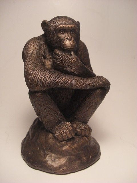 A sculpture of a chimpanzee in a thoughtful pose