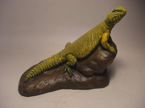 A painted sculpture of a lizard on a rock