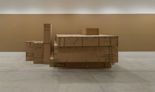 A photograph of some cardboard boxes in a brown-hued room