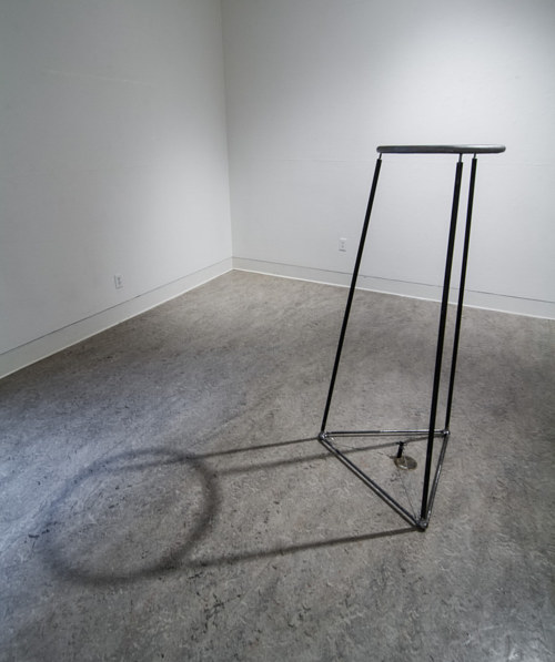 A metal sculpture casting an interesting shadow on the floor