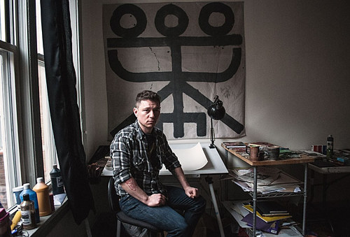 A photo of artist Elijah Burgher in his studio