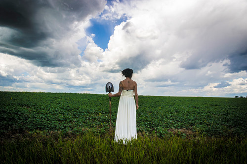 A performance piece with the artist standing in a field in a white dress