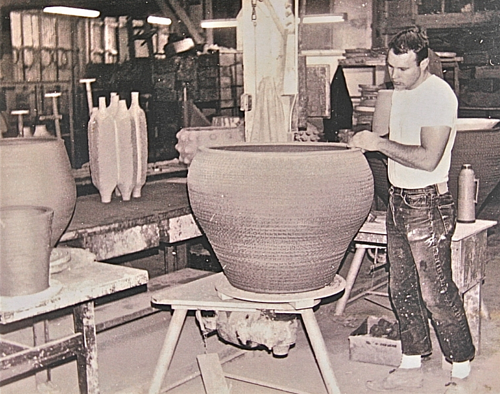 A photo of Michael Arntz working on a pottery piece in his studio